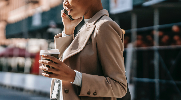 Woman on her phone holding a coffee